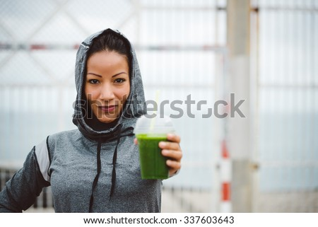 Successful urban sporty woman taking a rest for drinking nutritive detox smoothie. Fitness nutrition and healthy lifestyle concept.