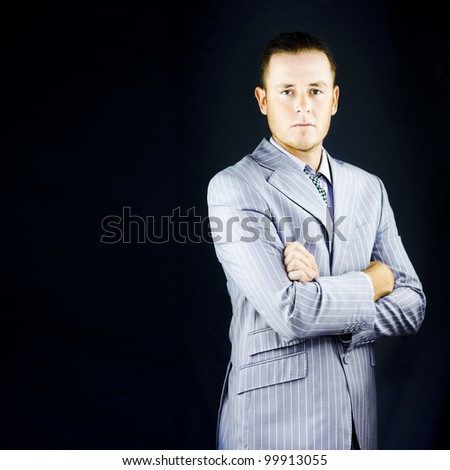 Successful wealthy influential young business man posing in a bespoke pinstripe suit with an air of authority and self-assurance against a dark background