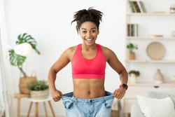 Successful Weight Loss. Happy African Woman After Slimming Showing Her Old Oversize Pants Standing Indoors, Smiling To Camera