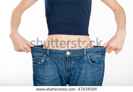 Successful weight loss, woman with too large jeans after a diet