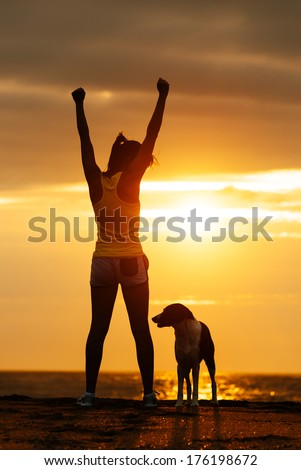 Successful woman and dog enjoying freedom on beautiful golden sunset. Fitness girl raising arms celebrating sport achievement with her pet.