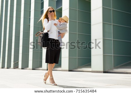 Successful woman going to work with baby in her hands #715635484