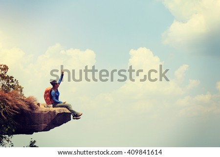 successful woman hiker enjoy the view on mountain top rock #409841614