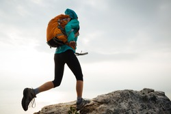 Successful woman hiker running to on seaside mountain peak cliff edge