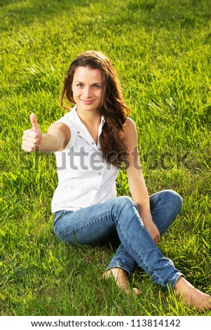 Successful woman holding her thumbs up in nature #113814142