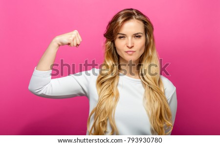 Successful woman raising hand in success gesture over pink background #793930780