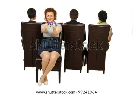 Successful woman sitting on chair out of the crowd and giving thumbs - stock photo