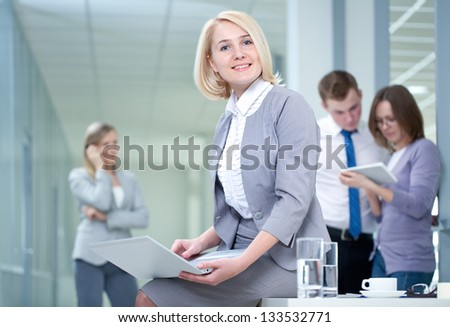 Successful woman with digital tablet and colleagues in the background