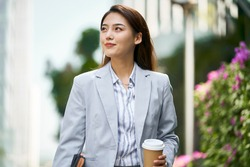 successful young asian female white collar office worker walking on street looking away holding cup of coffee