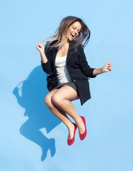 Successful young attractive laughing woman jumping up