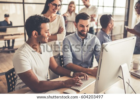 Successful young business people are using a computer and smiling while working in business center #604203497