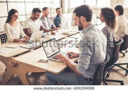 Successful young business people are using laptops and smiling while working in business center #604204088