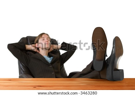 Successful, young business woman in a tailored suit resting with feet up on a desk. Image is isolated on a white background.