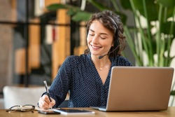 Successful young business woman working on laptop with headphones in a call center as a consultant. Happy businesswoman with headset translating and writing notes by listening to audio course.
