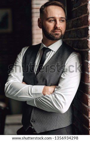 successful young businessman in a vest and tie. with a stylish and stylish haircut and beard