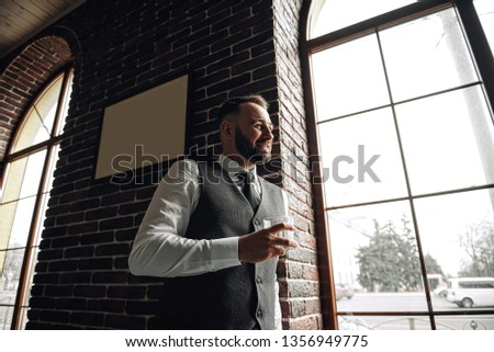 successful young businessman in a vest and tie. with a stylish and stylish haircut and beard. holding a glass of whiskey in his hands