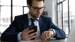 Successful young businessman in formal suit glasses busy checking modern smartwatch and smartphone at workplace, Caucasian male employer plan manage task on wrist hand watch, time management concept