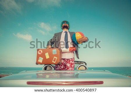 Successful young businessman on a beach. Man standing in the cabriolet classic car. Summer vacations and travel concept. Toned image #400540897