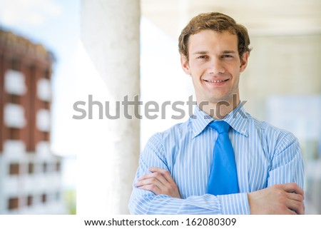 successful young businessman smiling, arms crossed looking, looking in the camera