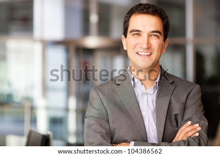 Successful young businessman with arms crossed and smiling