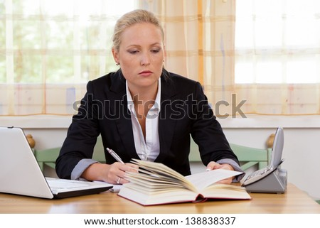 successful young businesswoman sitting at desk with laptop computer and fracture