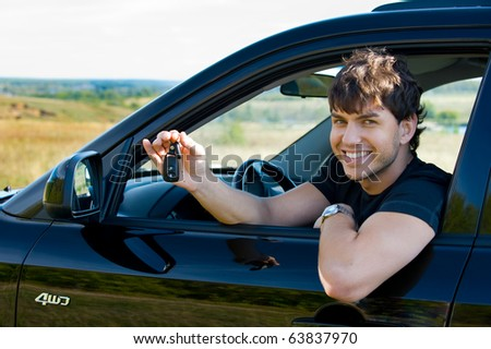 Successful young happy man showing the keys sitting in new car