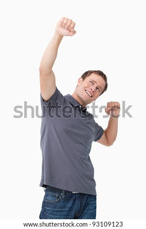 Successful young man celebrating against a white background