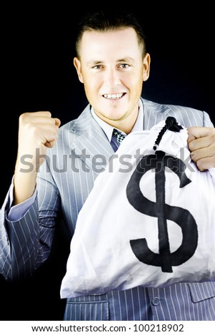 Successful young man in stylish grey suit raising his fist in jubilation at his latest success which is attested to by the large money bag full of dollars that is is gleefully clutching in his hand