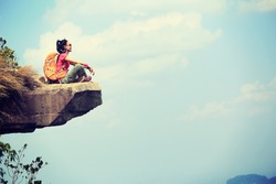 successful young woman backpacker sit on seaside mountain top cliff edge