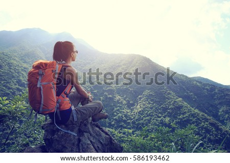 successful young woman hiker hiking on mountain peak
