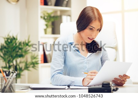 Successful young woman in the office brainstorming over business report.