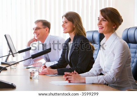 Successful young woman speaking in public on microphone sitting at the table in black comfortable chairs among her colleagues
