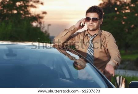 Successfull businessman on phone, sunset on back
