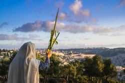 Succot (Feast of Tabernacles) in Jerusalem: Jewish man in a Tallit praying while waving the Four Species, with a view towards the Temple Mount, the Old City and the Mount of Olives