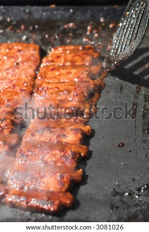 Succulent and saucy de-boned pork ribs on a gas powered. Shallow Depth of Field, focus on the back part of the front ribs