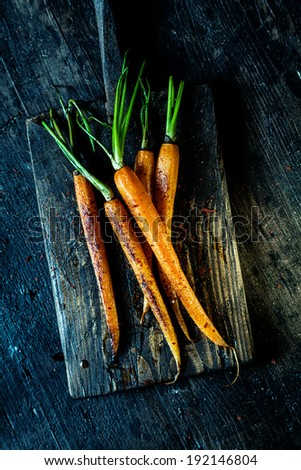 Succulent fried fresh young carrots served whole on an old rustic wooden chopping board for healthy vegetarian fare, overhead view