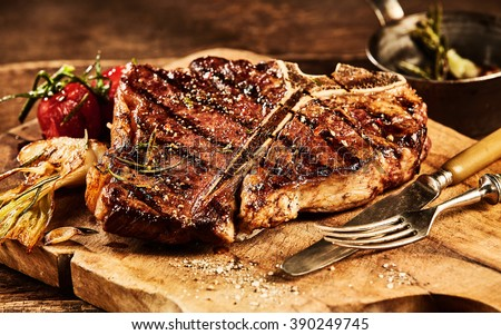 Succulent grilled large t-bone steak garnished with herbs, tomato and salt with fork and knife beside it on cutting board