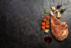 Succulent grilled tomahawk beef steak on the bone with red wine, seasonings, fresh rosemary and grilled vegetables on a black background, top view