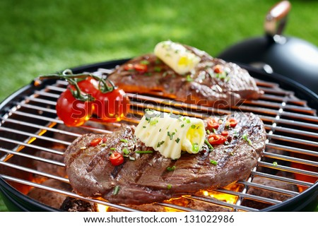 Succulent portion of lean steak topped with butter and herbs grilling on a grid over hot coals in a barbecue