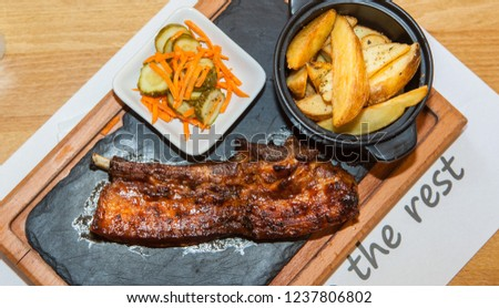 Succulent thick juicy portions of grilled fillet steak served with fries and vegetables on an old wooden board top view.