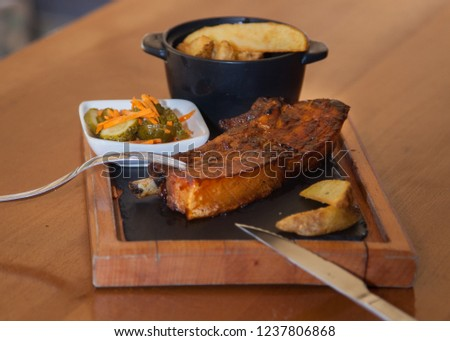 Succulent thick juicy portions of grilled fillet steak served with fries and vegetables on an old wooden board.
