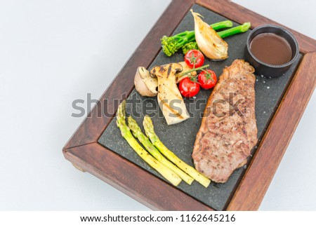 Succulent thick juicy portions of grilled fillet steak served with tomatoes and roast vegetables on an old wooden board. Gourmet food background concept