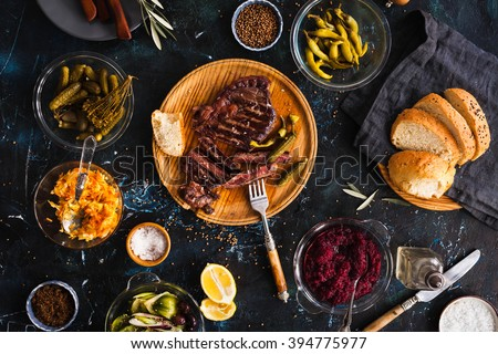 Succulent thick juicy portions of grilled fillet steak served with variety veggies dips, fermented veggies, cucumber and pepper marinated, bread buns on a old vintage table  Authentic dinner party. #394775977