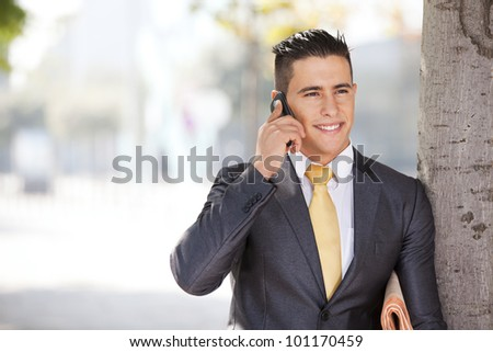 Sucessful and handsome businessman talking at his cellphone next to a tree