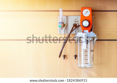 suction unit tube and storage tank for mucus of patient and oxygen flow regulator with tube scale for help breathing patients on wall in room at hospital Foto stock ©