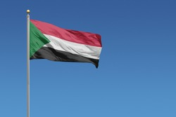 Sudan flag in front of a clear blue sky
