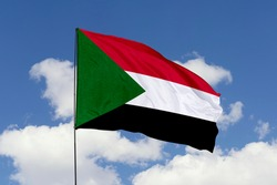Sudan flag isolated on the blue sky with clipping path. close up waving flag of Sudan. flag symbols of Sudan.