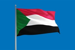 Sudan national flag waving in the wind on a deep blue sky. High quality fabric. International relations concept.