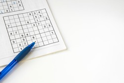 sudoku puzzle book with blue pen, against white background. space for text