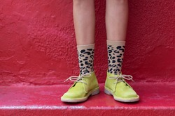 Suede Boots with Animal Print Socks on Red Background